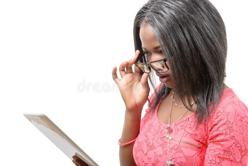 Femme assez jeune d'afro-américain avec les lunettes et le comprimé c photographie stock