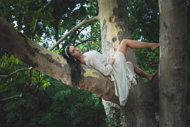 Femme assez jeune de cheveux foncés dans le mensonge aux pieds nus de robe romantique dessus photographie stock libre de droits