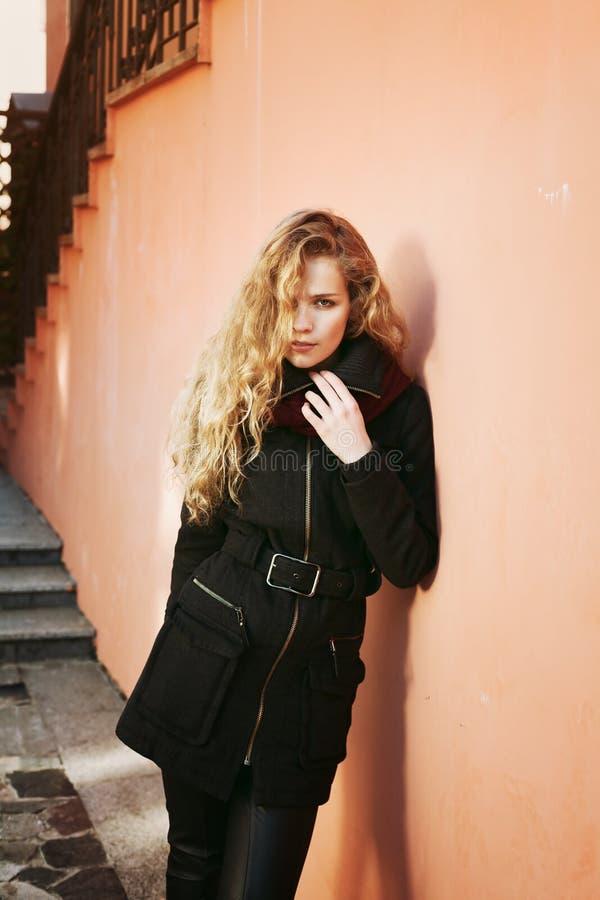 Femme assez jeune de mode avec de longs cheveux bouclés regardant in camera et posant extérieur près du mur photographie stock libre de droits