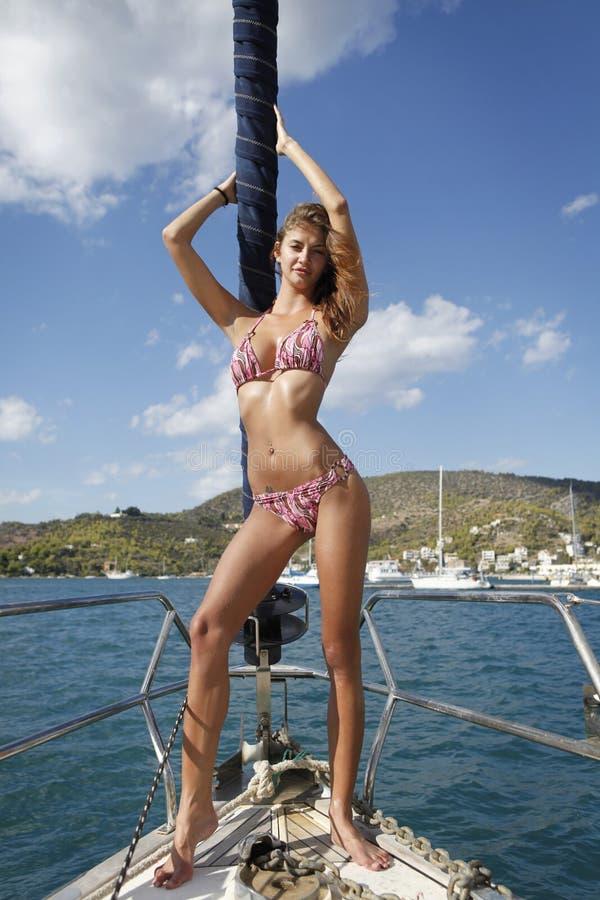 Femme assez jeune posant sur le yacht photographie stock