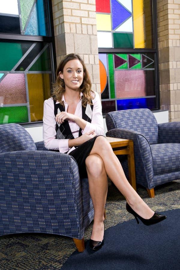 Femme assez jeune s'asseyant sur la présidence de salle d'attente image libre de droits