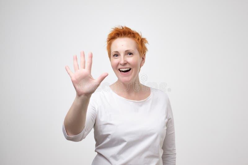 Femme assez mûre avec les cheveux rouges dans le T-shirt blanc montrant le geste de main de 5 ou cinq doigts photos libres de droits