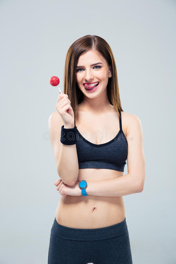 Femme assez sportive tenant la lucette et montrant le tonue photo libre de droits
