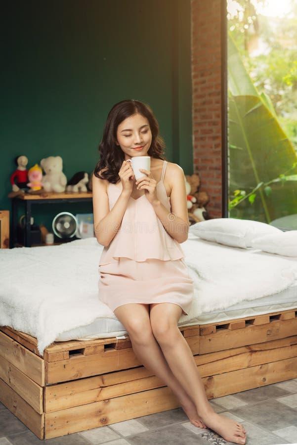 Femme assez vietnamienne appréciant son café de matin à la maison image libre de droits