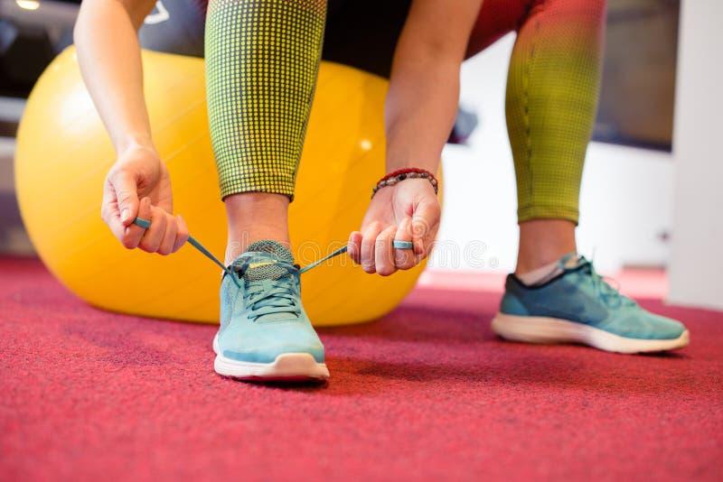 Femme attachant la chaussure au gymnase image libre de droits