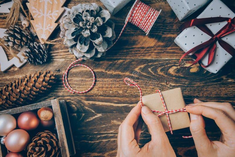 Femme attachant le boîte-cadeau enveloppé en papier de métier avec le ruban rouge blanc rayé Les cônes de pin de boules de décora photographie stock