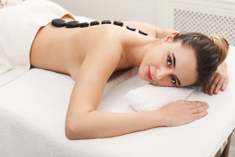 Femme atteignant le massage chaud de pierres le salon de station thermale photo libre de droits
