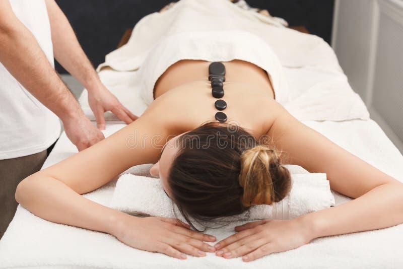 Femme atteignant le massage chaud de pierres le salon de station thermale photos stock
