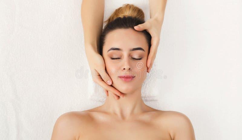 Femme atteignant le massage facial professionnel le salon de station thermale image libre de droits