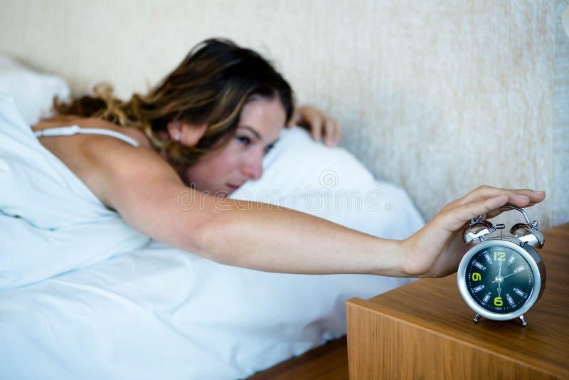 femme atteignant pour arrêter son réveil image stock