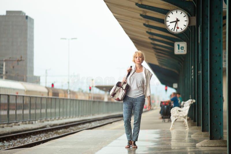 Femme attendant à la plate-forme du sac d'épaule de vintage d'incidence de gare ferroviaire image libre de droits