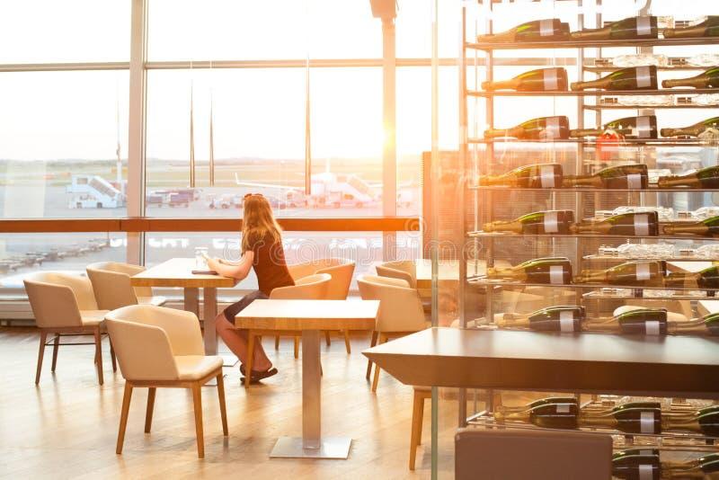 Femme attendant dans le café dans le terminal d'aéroport et regardant la fenêtre l'avion images stock