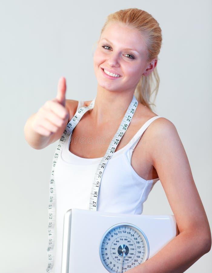 Femme attirant avec le pouce vers le haut de retenir des échelles photographie stock