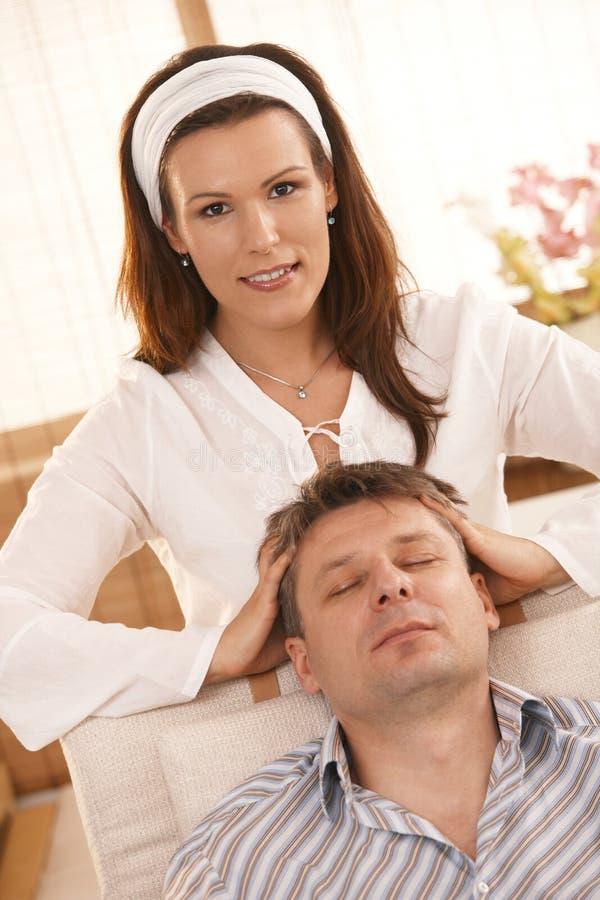 Femme attirant donnant le massage principal à l'homme photographie stock libre de droits