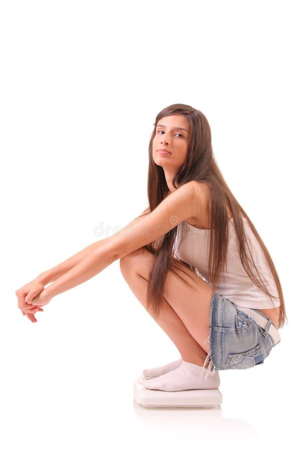 Femme attirant sur une échelle de poids photo stock