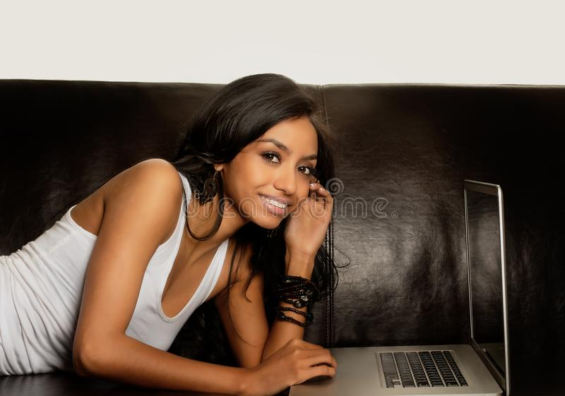 Femme attirante à l'aide de l'ordinateur portatif image stock