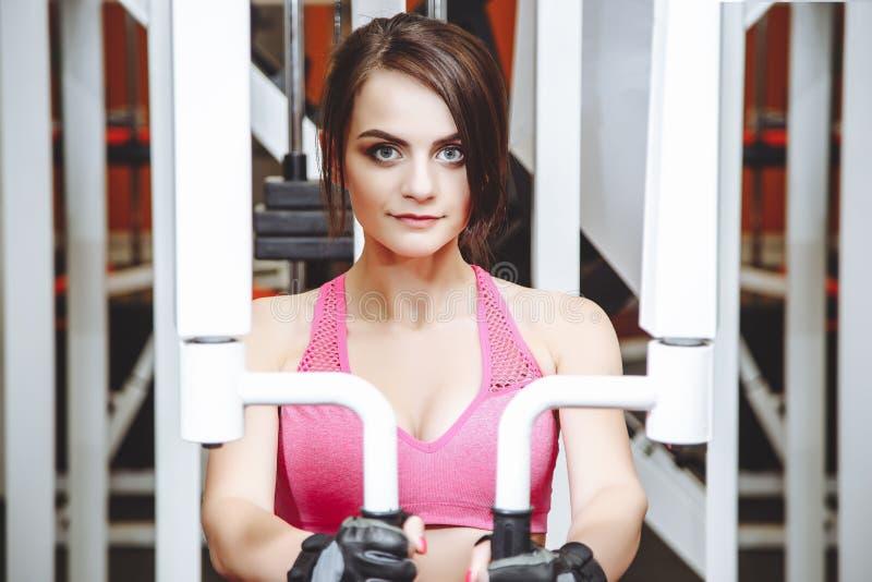 Femme attirante établissant sur la machine de papillon Bodybuilder de jeune femme faisant l'exercice pour le coffre dans le gymna photographie stock