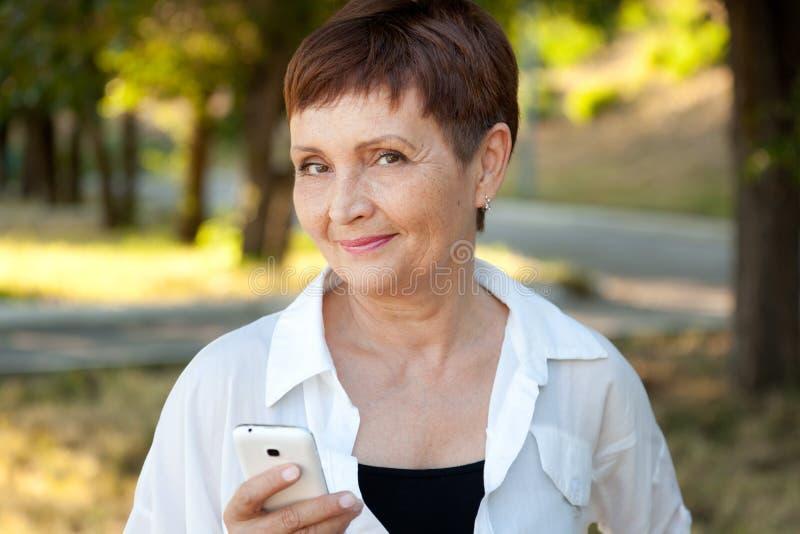 Femme attirante 50 ans en parc avec un téléphone portable image stock