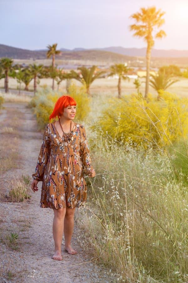 Femme attirante avec la belle robe appréciant la nature images stock
