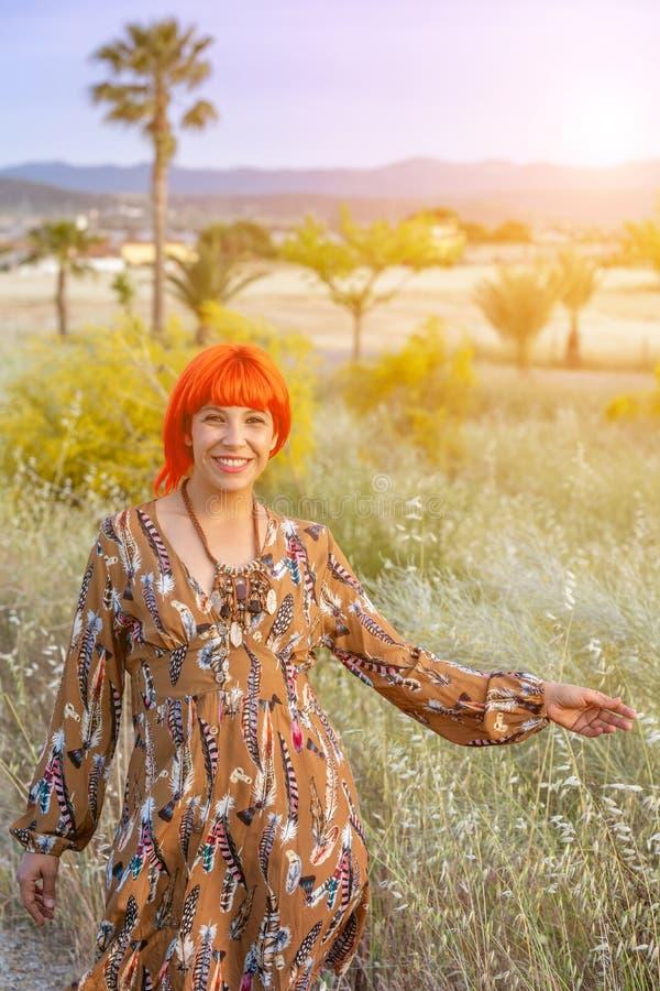 Femme attirante avec la belle robe appréciant la nature photographie stock