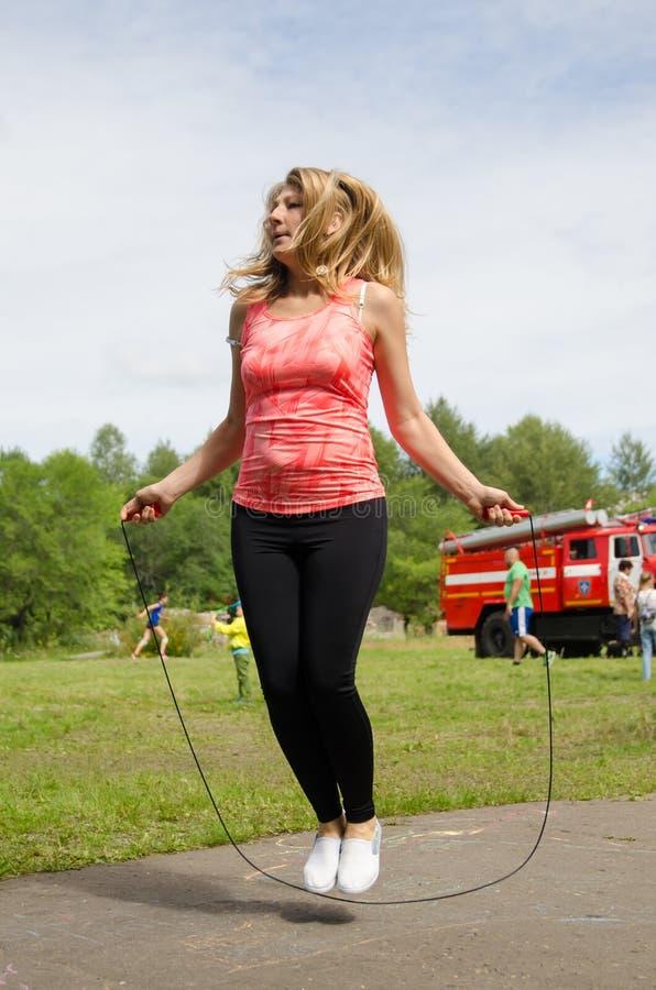Femme attirante avec la longue corde de sauts de cheveux à la concurrence amateur en été image stock