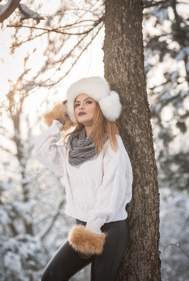 Femme attirante avec le chapeau et la veste blancs de fourrure appréciant l'hiver Vue de côté de la pose blonde à la mode de fill photographie stock libre de droits