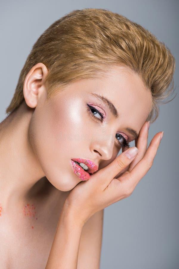 femme attirante avec le scintillement sur des lèvres touchant le visage et regardant la caméra image libre de droits