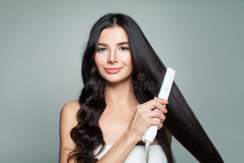 Femme attirante avec les cheveux bouclés et les longs cheveux droits images libres de droits
