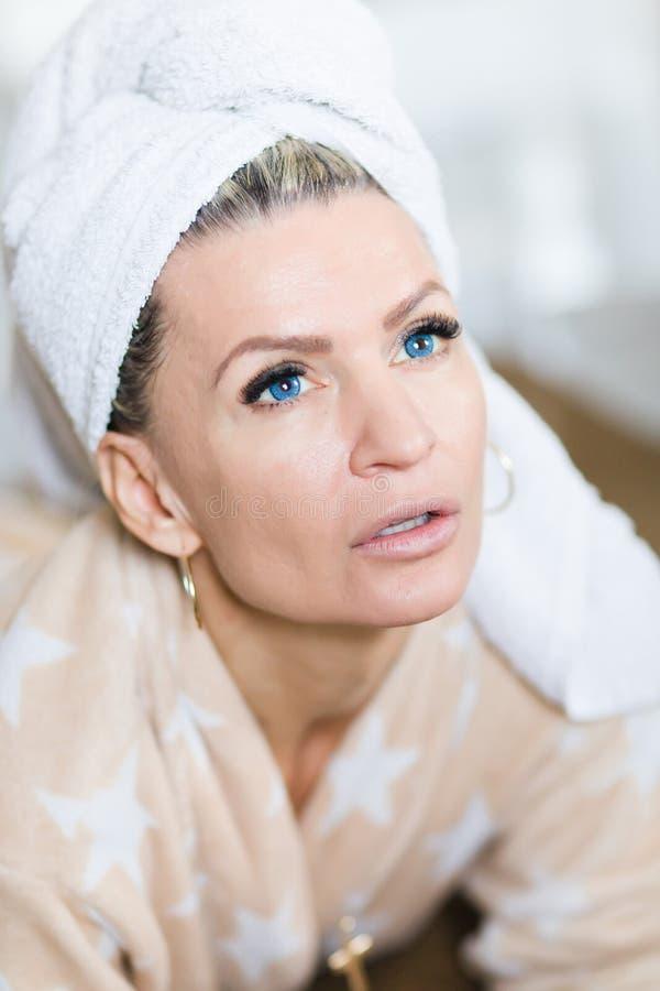 Femme attirante avec les verres de contact bleus avec la serviette sur la tête après relaxation photos stock