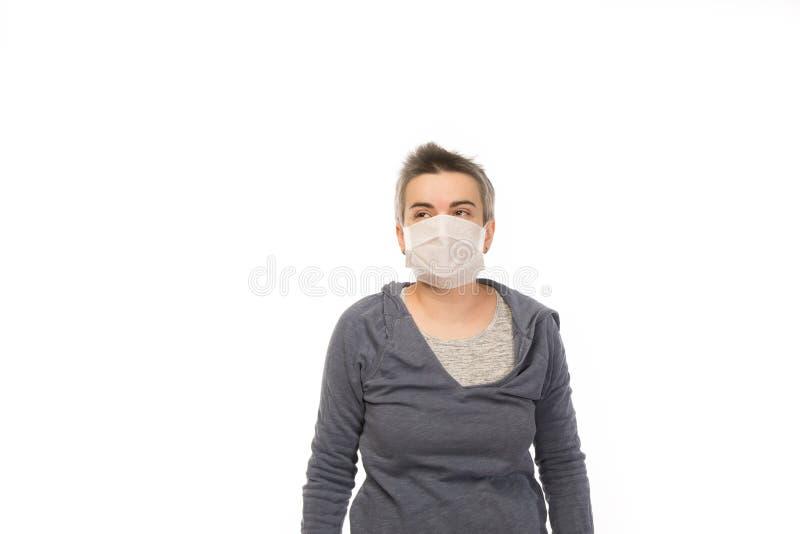 Femme attirante blanche de brune avec les cheveux courts portant un masque pendant une épidémie de grippe D'isolement sur le blan images libres de droits