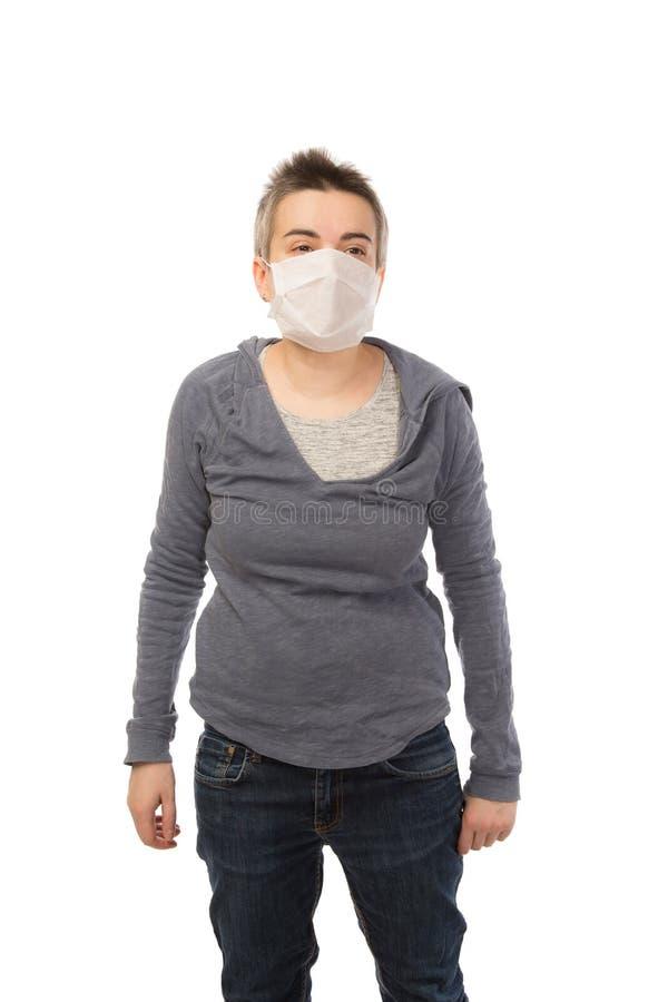 Femme attirante blanche de brune avec les cheveux courts portant un masque pendant une épidémie de grippe D'isolement image stock