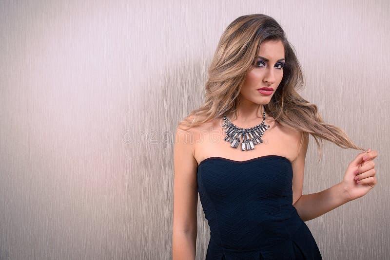 Femme attirante blonde avec de longs cheveux onduleux, sur le forma de paysage photo stock