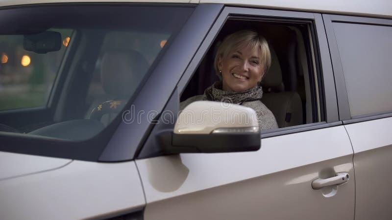 Femme attirante blonde mûre souriant et regardant directement du salon de voiture photographie stock libre de droits