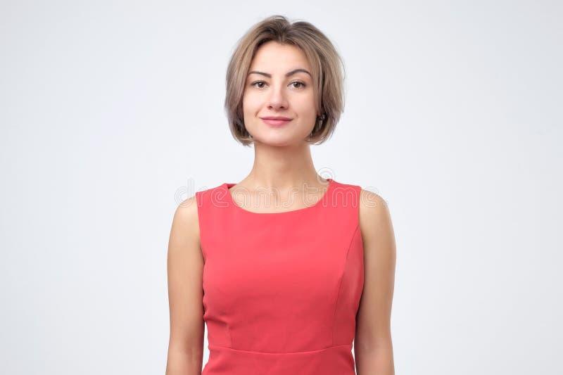 Femme attirante charismatique dans la robe rouge, souriant gaiement tout en se tenant sur le fond gris image stock