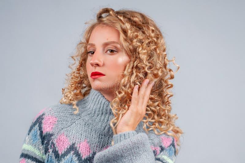 Femme attirante d'étudiant avec les cheveux bouclés habillés dans le chandail chaud image stock