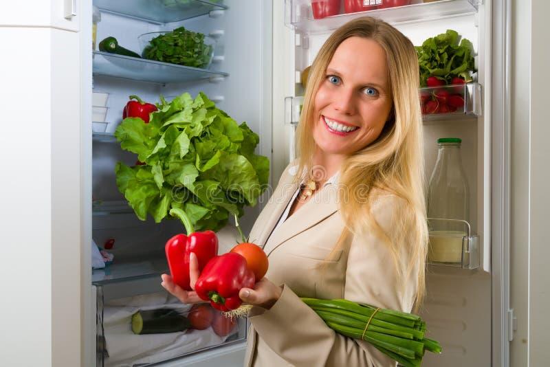 Femme attirante d'affaires montrant des légumes pour la consommation saine photos stock