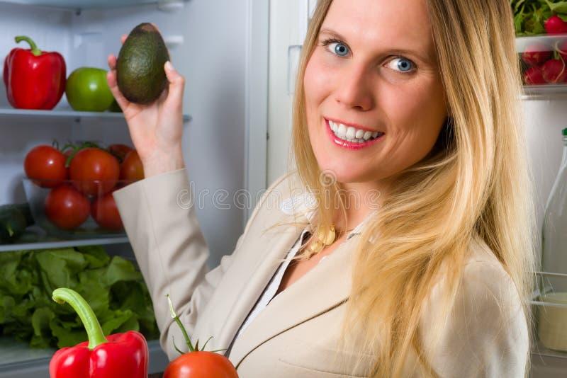Femme attirante d'affaires montrant des légumes pour la consommation saine photo stock