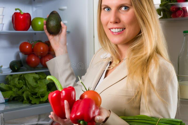 Femme attirante d'affaires montrant des légumes pour la consommation saine image libre de droits