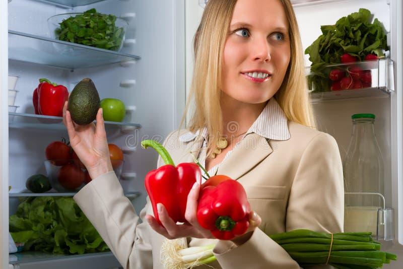 Femme attirante d'affaires montrant des légumes pour la consommation saine photographie stock