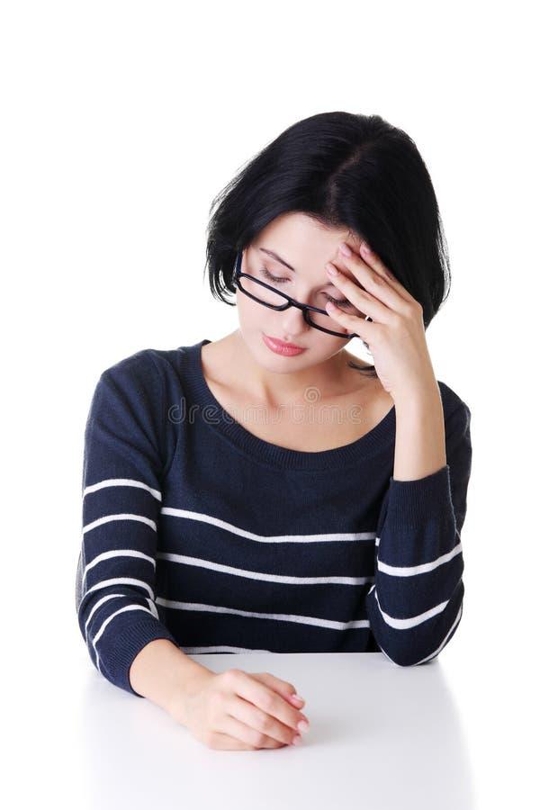 Femme attirante dans des lunettes se reposant par la table. photos libres de droits