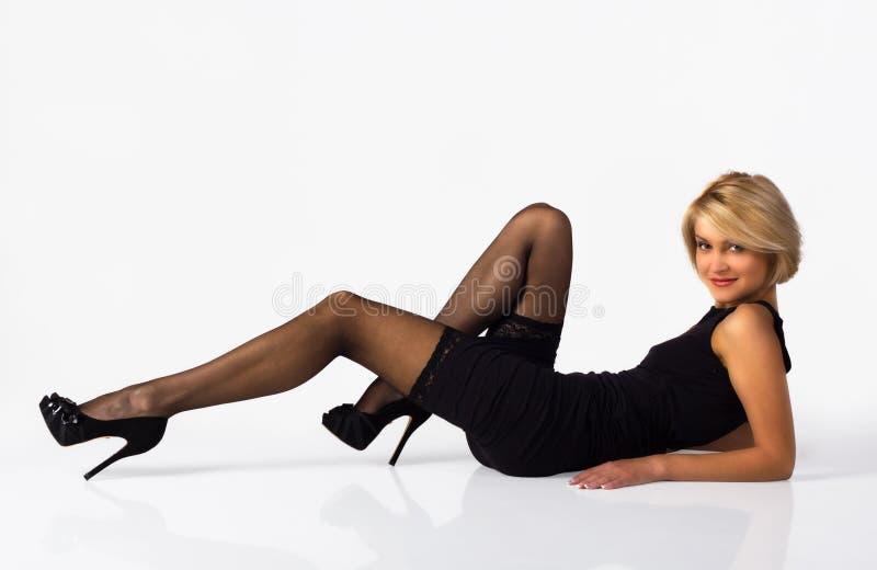 Femme attirante dans la robe noire posant le mensonge sur le plancher images libres de droits