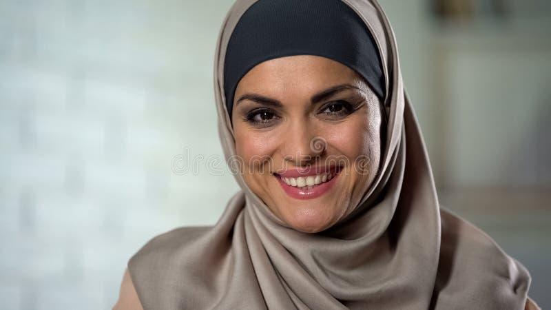 Femme attirante dans le hijab souriant ? la cam?ra, beaut? arabe de mode, f?minit? image libre de droits