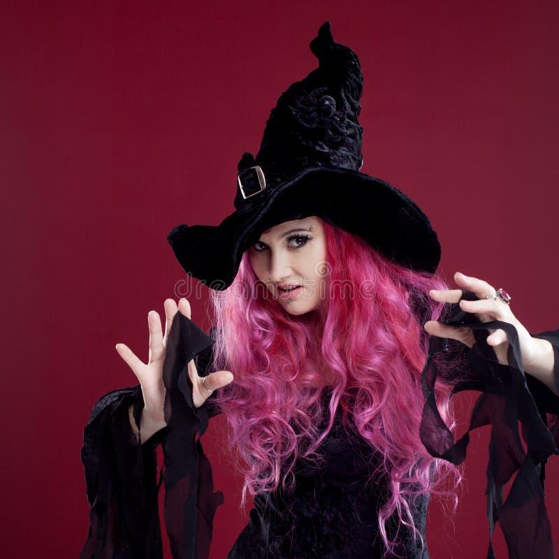 Femme attirante dans les sorcières chapeau et costume avec les cheveux rouges Veille de la toussaint photo libre de droits