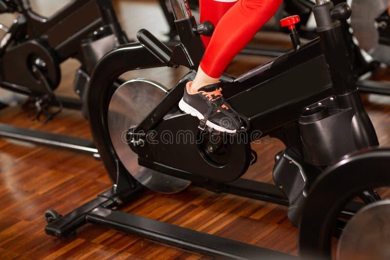 Femme attirante dans un costume rouge de sports dans le gymnase, montant sur le vélo stationnaire de vitesse haut ?troit de jambe photographie stock libre de droits