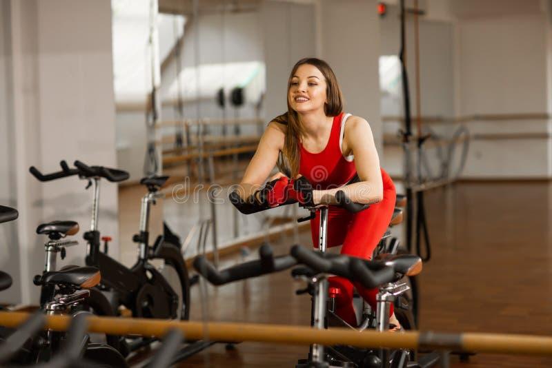 Femme attirante dans un costume rouge de sports dans le gymnase, montant sur le vélo stationnaire de vitesse R?flexion dans le mi image libre de droits