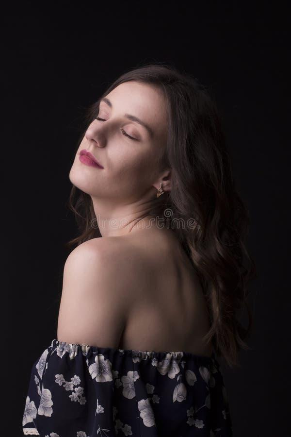 Femme attirante de brune avec les yeux fermés au studio photos stock