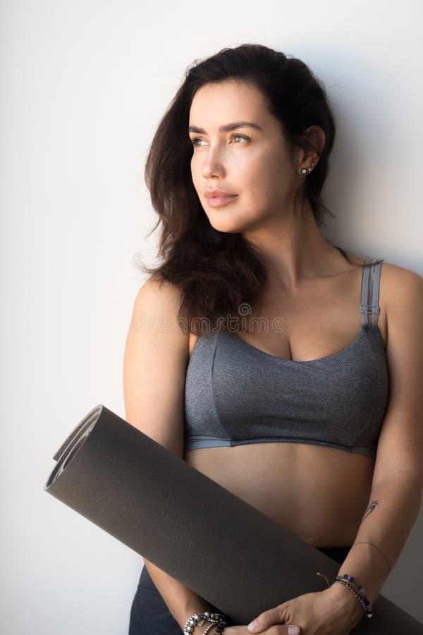 Femme attirante de jeune yogi tenant le tapis de yoga ou de forme physique photo stock