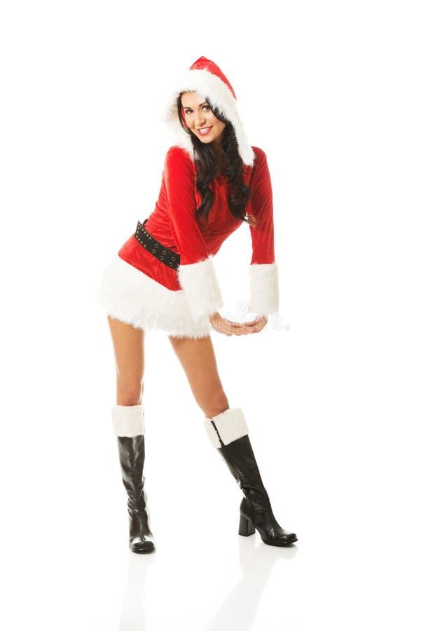 Femme attirante de Santa se tenant à califourchon sur et incliné, regardant à l'appareil-photo photo stock