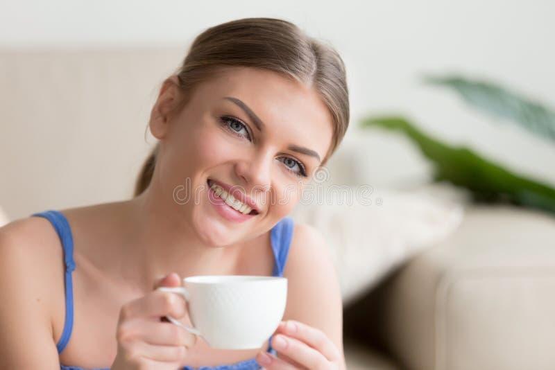 Femme attirante de sourire de jeunes appréciant le café regardant l'appareil-photo photographie stock libre de droits