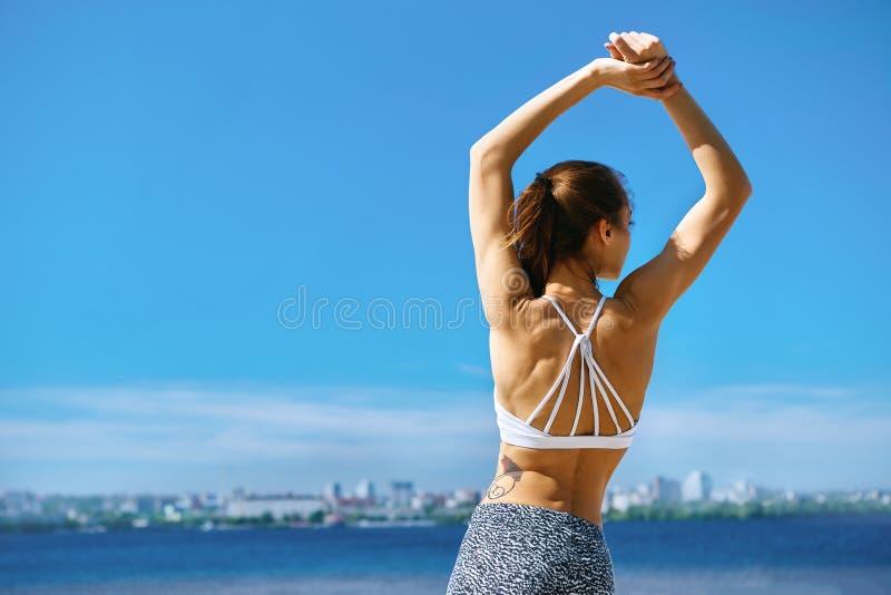 Femme attirante de sports avec le corps convenable bronzé posant avec les bras augmentés sur la plage avec le fond de ville contr photographie stock libre de droits
